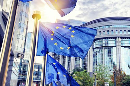 flagi unijne w tle biurowce